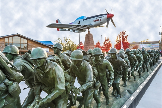 "The P-51 ""Donna K"" soars above the ""Storming the Beach"" bronze statue."