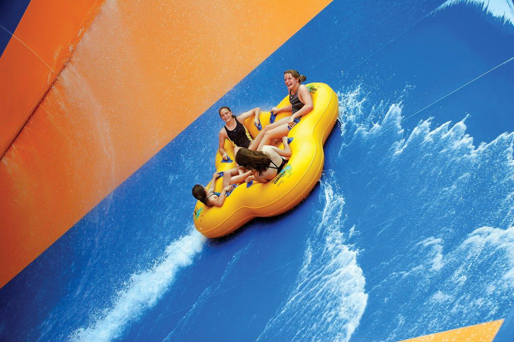 4 girls go for a ride on a blue and orange water slide at Williamsburg water parks
