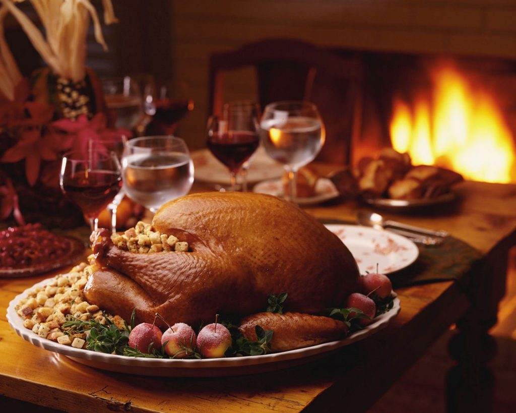 A cooked turkey on a white platter with stuffing and vegetables. The platter is on a wooden table with wine glasses in front of a fireplace
