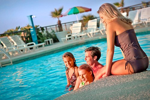 Two daughters, a dad and a Mom hang out by the pool during their Myrtle Beach Spring Break