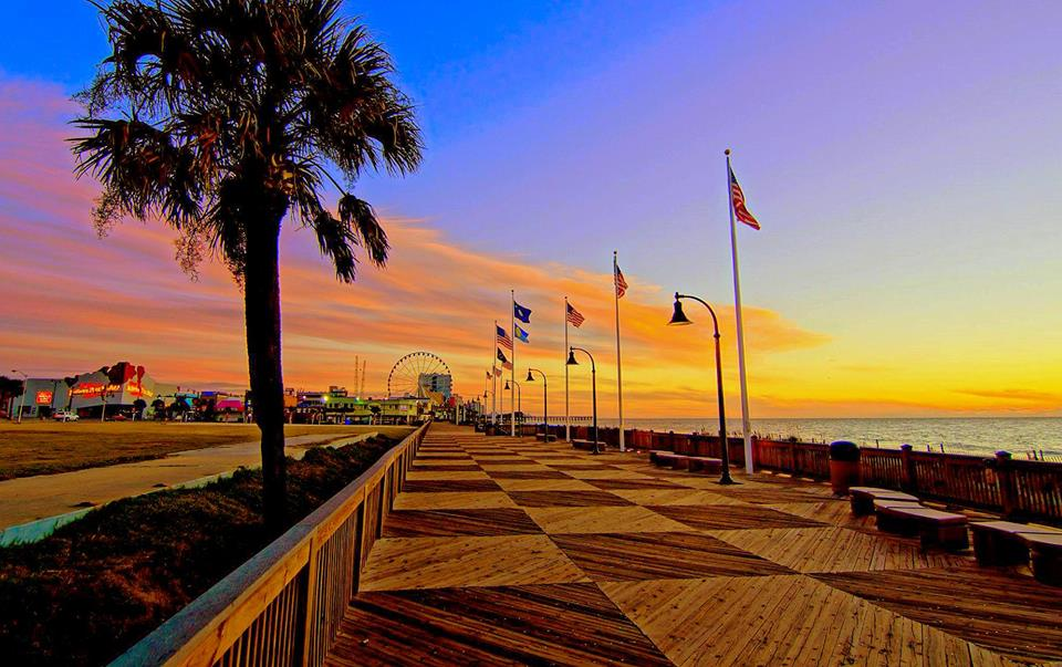 The Myrtle Beach boardwalk at sunset with flags and palm trees lining the way
