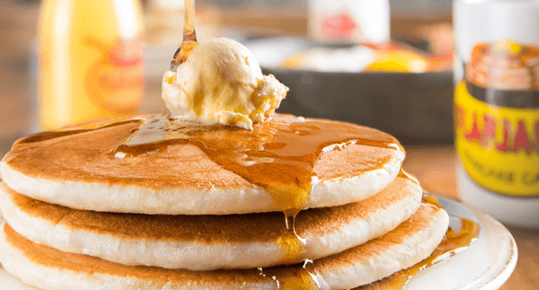 A stack of pancakes from Flapjack's with a dollop of butter and syrup