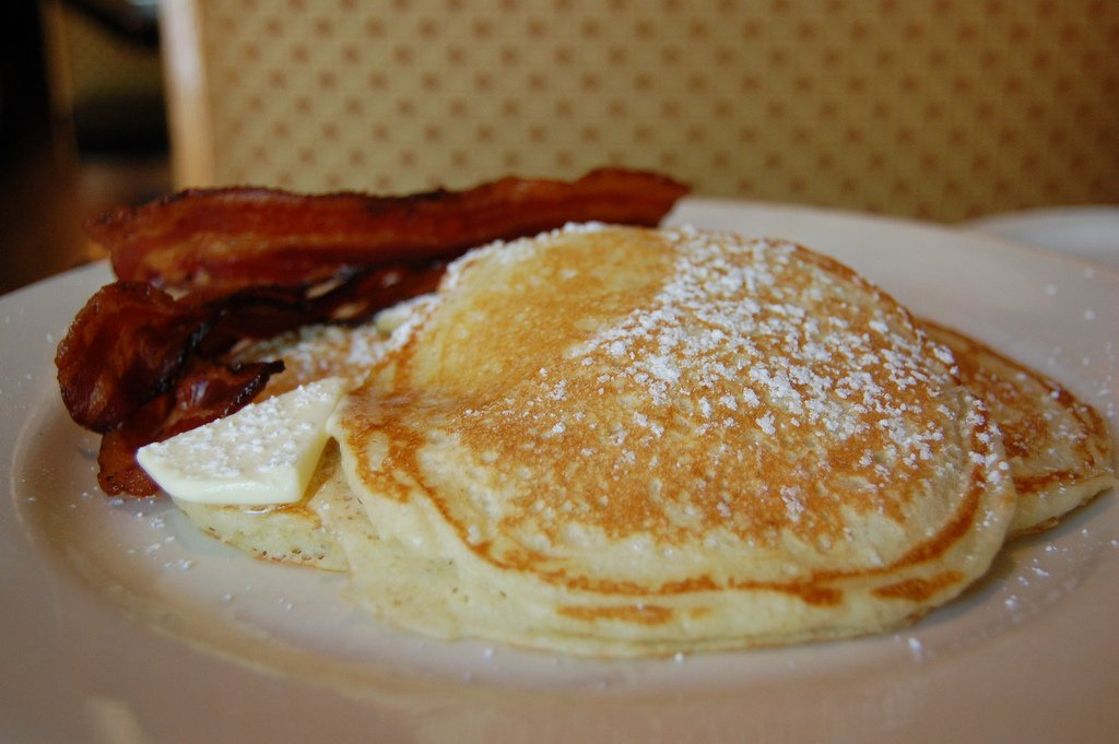 A stack of pancakes next to a side of bacon