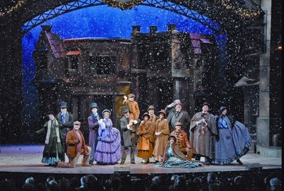 The cast of A Dicken's Christmas Carol performs at Silver Dollar City while snow falls.