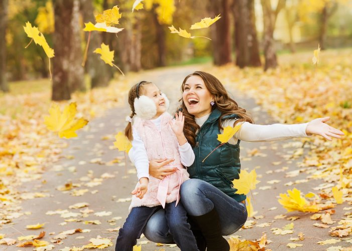 A woman and a little girl embrace the yellow falling leaves during a Branson Thanksgiving Day