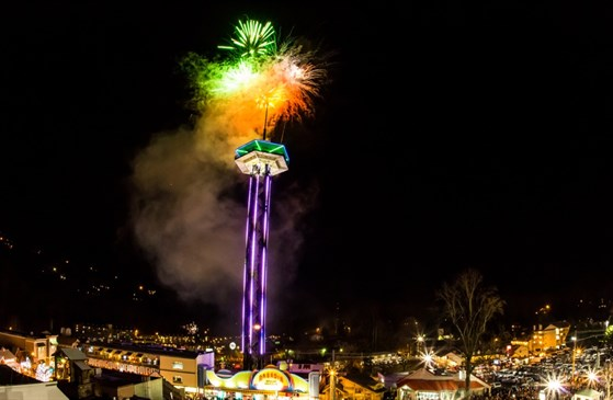 Orange and green fireworks explode over the Gatlinburg space needle, decorated for Gatlinburg's New Year's Eve