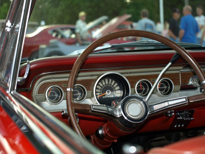 The thin steering wheel of a red antique, classic car.