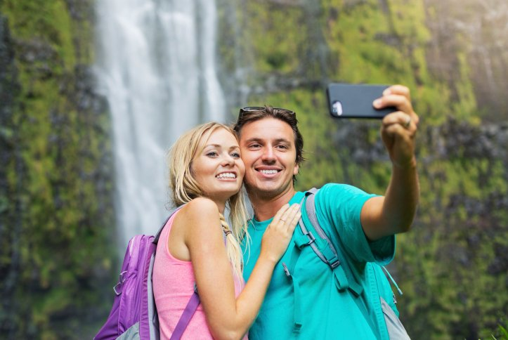 A couple takes a selfie at a waterfall in Oahu