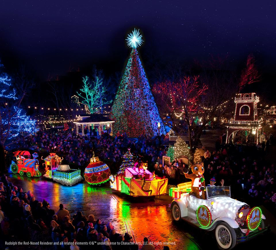 A Christmas parade filled with neon themed floats, and a lit up massive Christmas tree
