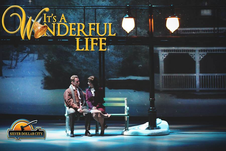 A man and a woman sit on a park bench during a production of It's a Wonderful Life