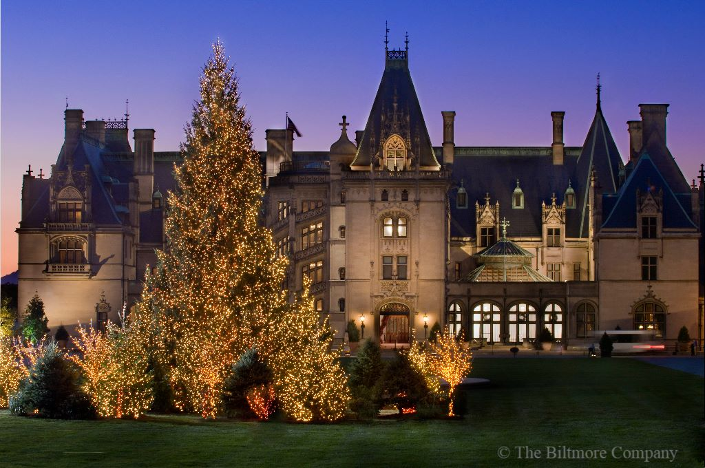 A giant Christmas tree is stationed in front of the towering Biltmore Estate