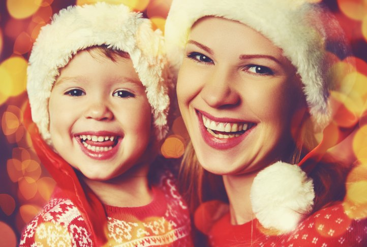 A child and young woman wear Santa hats and red Christmas sweaters and smile into the camera.