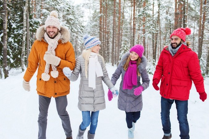Friends dressed in winter coats, hats, scarves, and mittens laugh and walk through a snowy forest