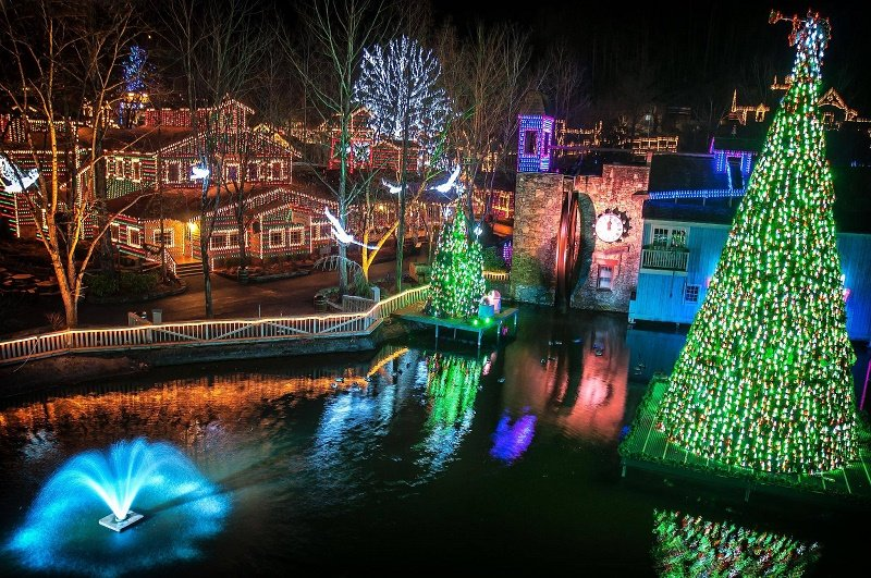 Dollywood's theme park grounds lit up with Christmas lights. Sights include a massive Christmas tree with green lights, a blue water fountain and trees with white lights.