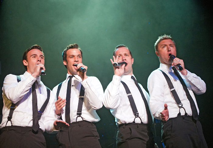 Four men wearing white dress shirts with suspenders sing into microphones in front of a green backdrop