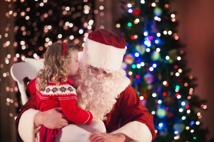 A little girl whispers into Santa Claus' ear, who is sitting on a white rocking chair in front of a Christmas tree with multi-colored lights.