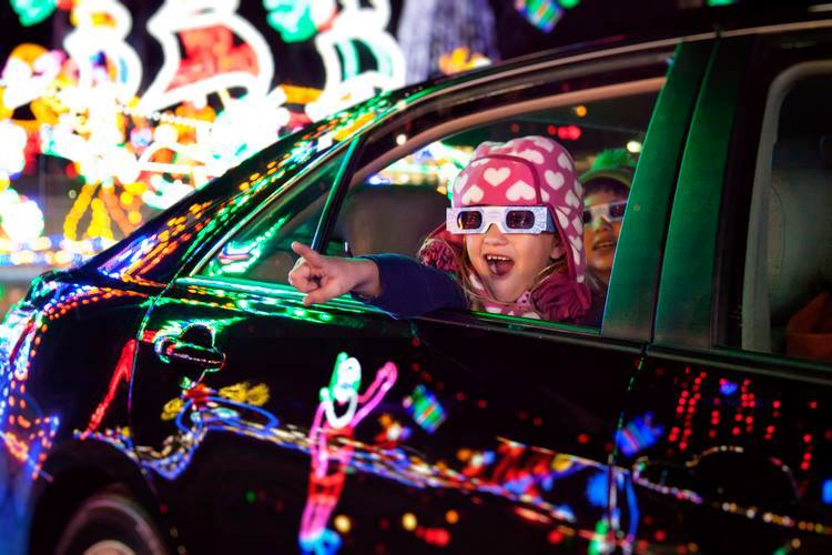 A young girl wearing 3D glasses and a winter hat inside a black car points at the Christmas lights at Shadrack's Christmas Wonderland in Pigeon Forge.