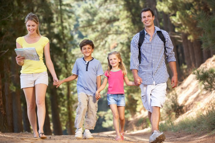 A happy family hikes through the woods during their Pigeon Forge Spring Break.