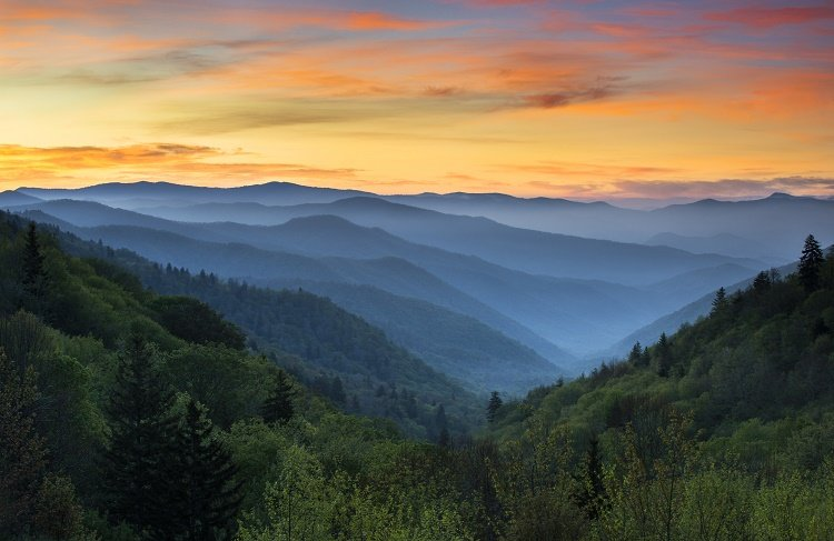 The sun sets over the Smoky Mountains creating shades of blue, green, red, and yellow.