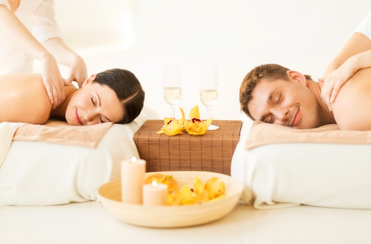 A man and woman receive a couples massage surrounded by yellow candles and glasses of champagne.