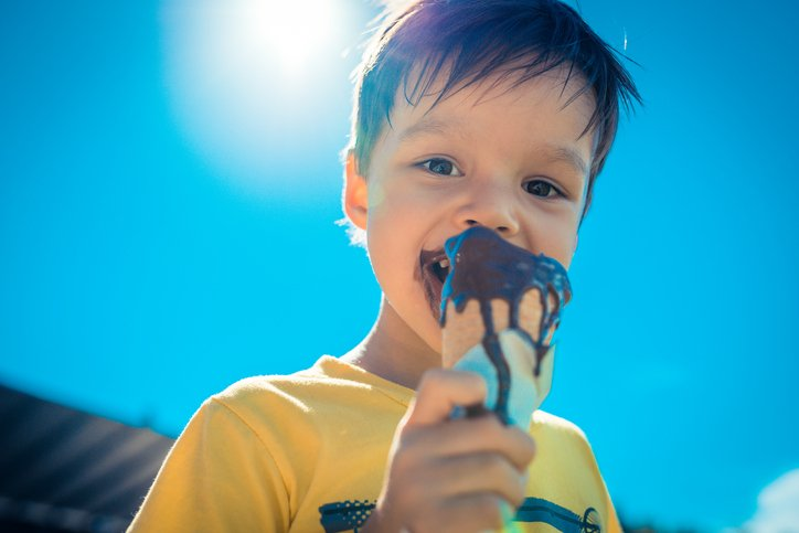 3 year old Asian Caucasian boy eats a melting chocolate ice-cream on the beach in the hot summer sun