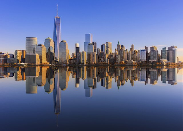 The NYC skyline is reflected into the blue river