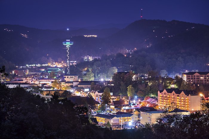 Downtown Gatlinburg lit up with neon lights at night against a Smoky Mountain backdrop