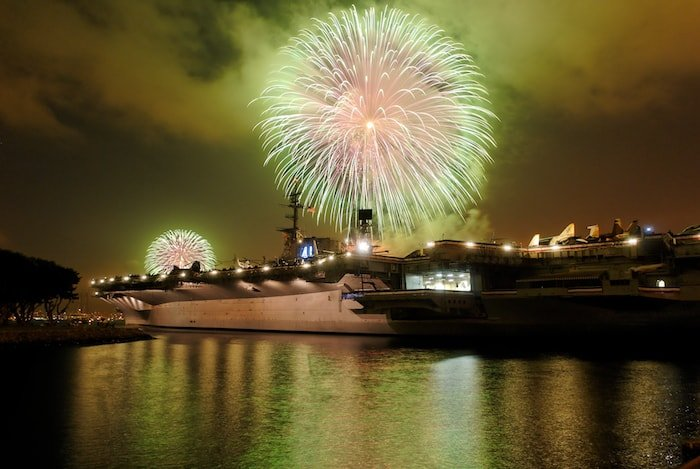 Fireworks explode over the USS Midway Museum at night.