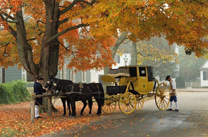 Horse and buggy is maintained by two colonial men at Colonial Williamsburg during autumn