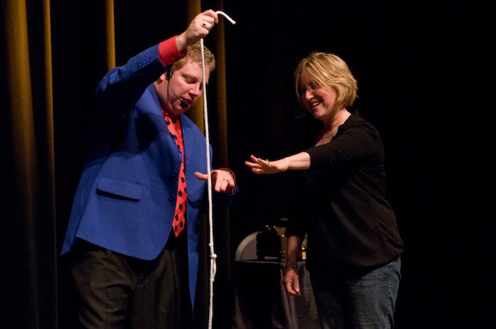 Magician performs a magic trick with a woman on stage.