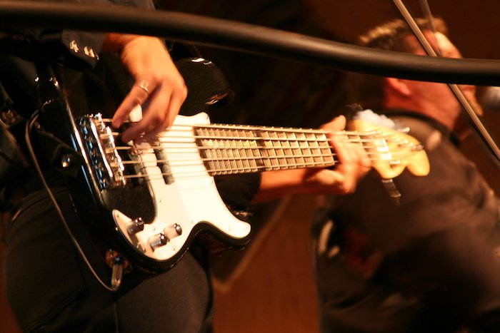 Musician plays a 5-string bass on stage.