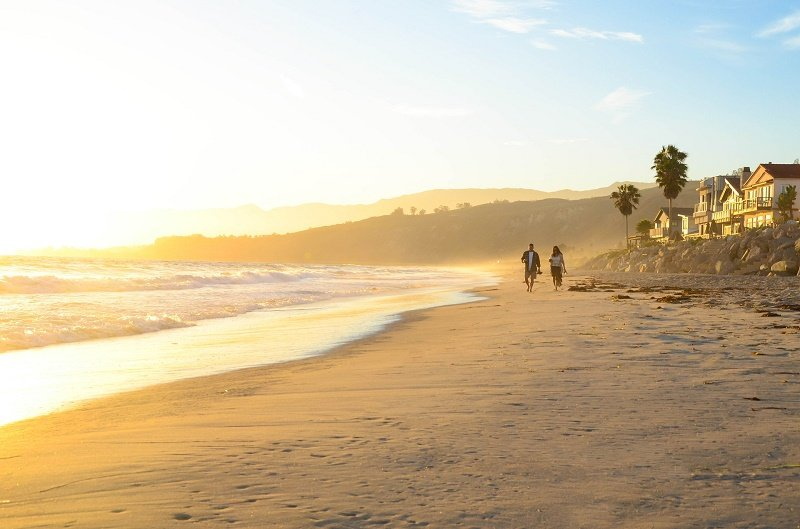 Man and woman stroll along the beach at sunset in Los Angeles