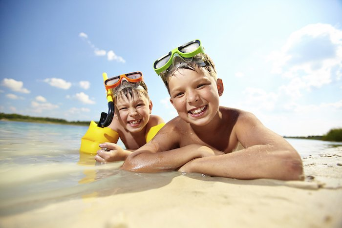 Two young boys in snorkel gear lay on the sand next to the ocean