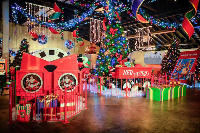 Santa's Workshop at Dollywood with larger than life toys, a Christmas tree with ornaments, and hundreds of holiday lights strung throughout the shop