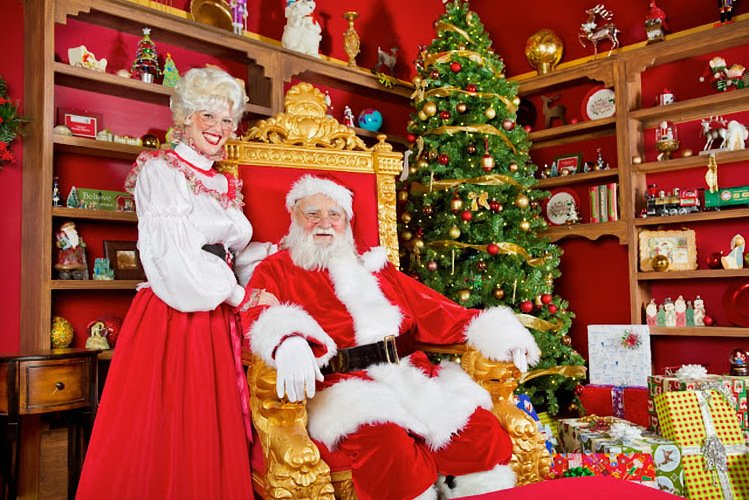 Santa Claus sits in a gold throne next to Mrs. Claus in a room filled with red, white, and gold holiday decor and a Christmas tree.
