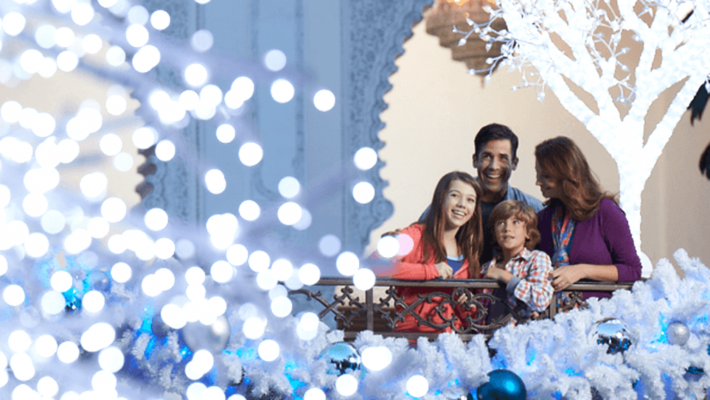 A family looks at the blue and white holiday decor at Busch Gardens Christmas Town in Tampa, Florida