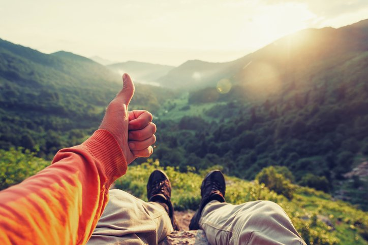 Happy male traveler showing thumb up in summer mountains at sunset, point of view shot