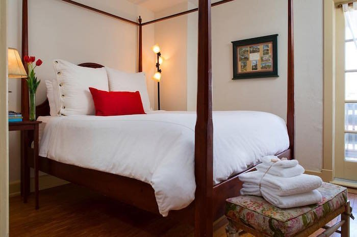A white bed with a red pillow and brown bed posts at the Fife and Drum Inn in Williamsburg, VA