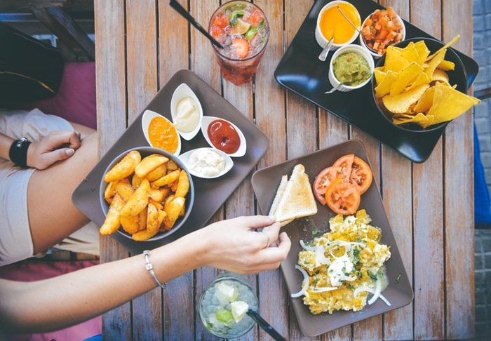 A woman eats lunch with friends, which includes nachos, fries, and various sauces, along with a fruity beverage