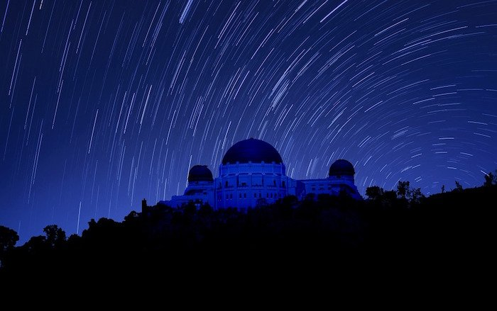 Griffith Observatory timelapse picture with stars orbiting the structure under a royal blue sky