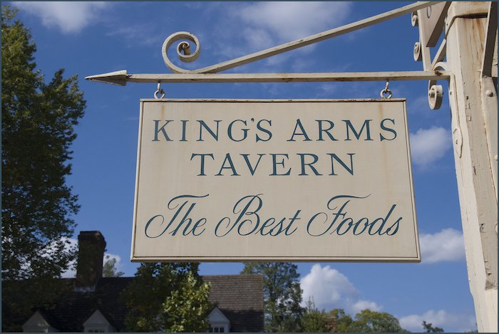 "A historic sign which says ""King's Arms Tavern The Best Foods"""
