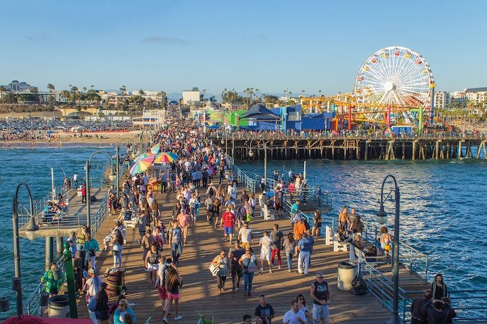 The Santa Monica pier packed with tourists and the iconic Ferris Wheel on a sunny day