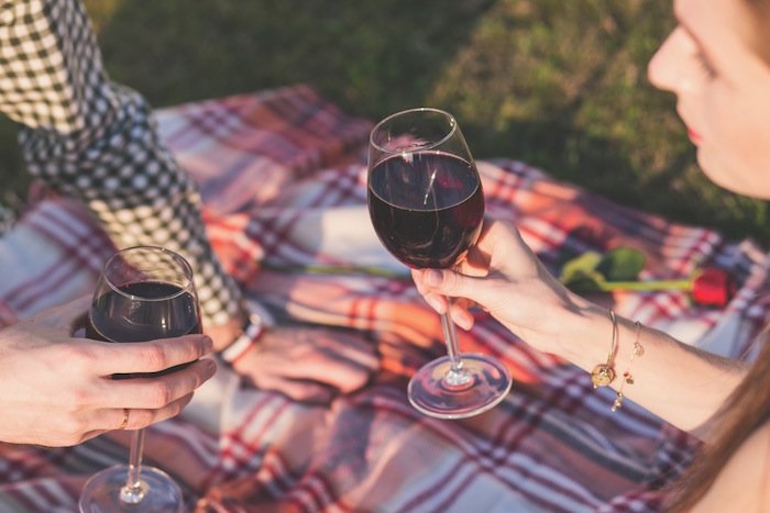 A couple sits on a red plaid blanket and enjoys a glass of red wine together on a romantic picnic