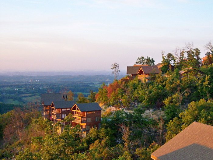 Smoky Mountain cabins rest on the mountainside surrounded by forests overlooking the town below