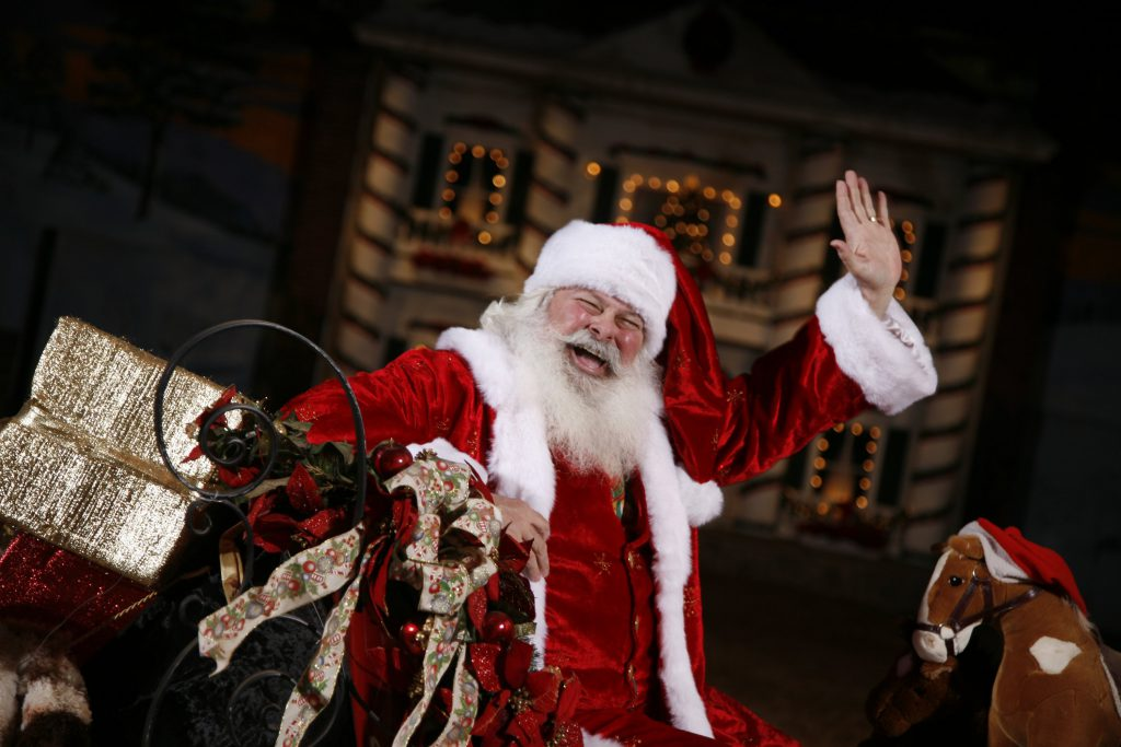Santa Claus sits on his sleigh adorned with Christmas decorations and waves to the show crowds