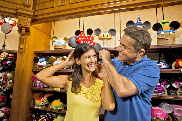 A man and woman try on Minnie Mouse ears during their first Disney World trip.