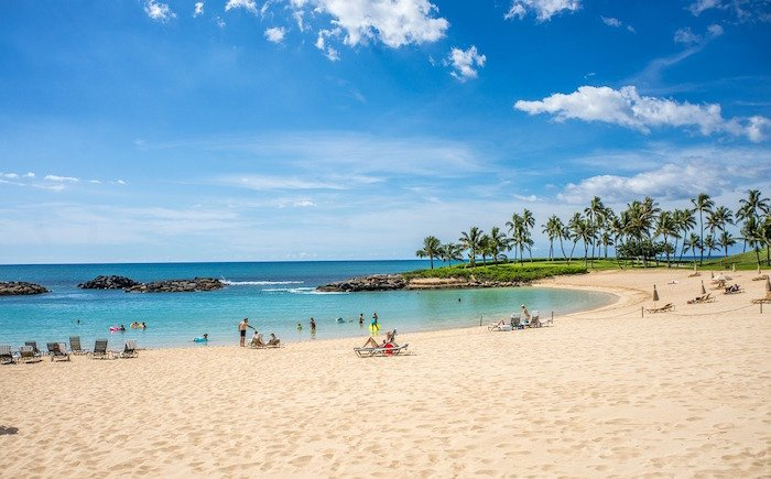 A turquoise Hawaii lagoon is surrounded by small groups of people enjoying the day on the beach