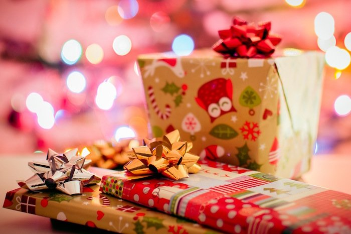 Christmas presents wrapped in holiday paper with red, gold, silver, and green decorations