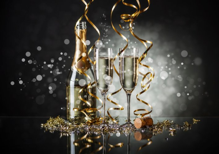 Two champagne classes are filled and standing next to a bottle while gold streamers and confetti fall from the sky.