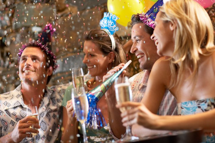 Adults hold filled champagne glasses while wearing New Year's Eve party hats. Confetti falls from the sky.